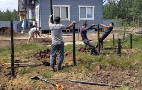 Сотрудники делают монтаж свай и обвязки для дома